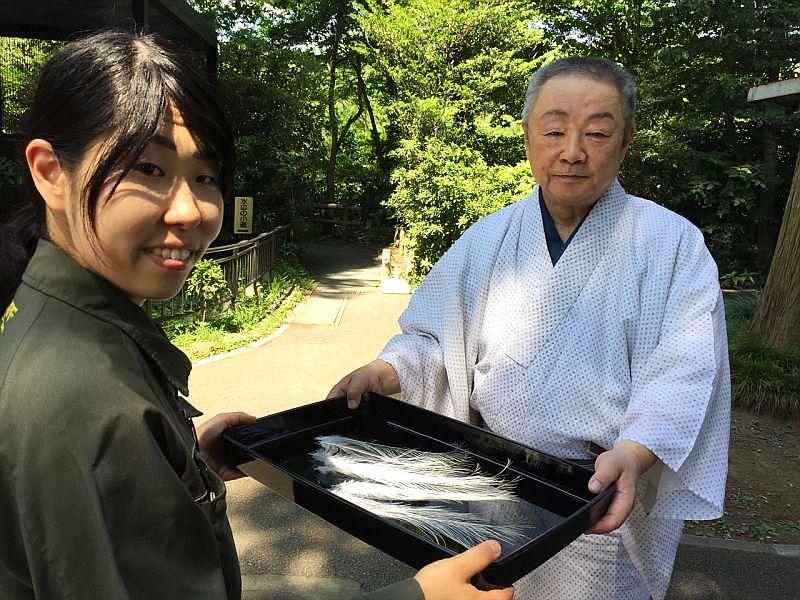 コサギ飼育担当の東條裕子さんから宝生流能楽師の東川光夫さんへ羽根を譲渡する様子