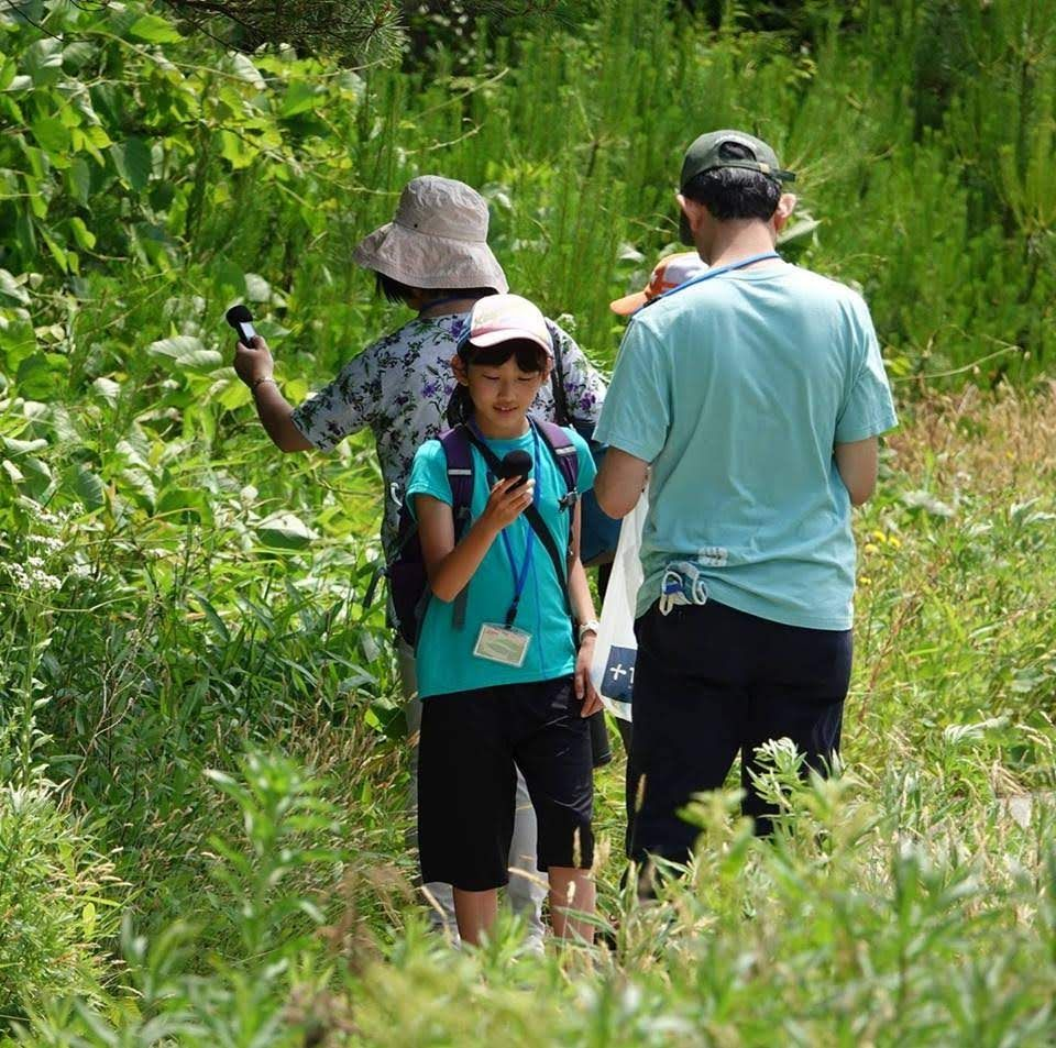 草原で音集めをする参加者(写真)