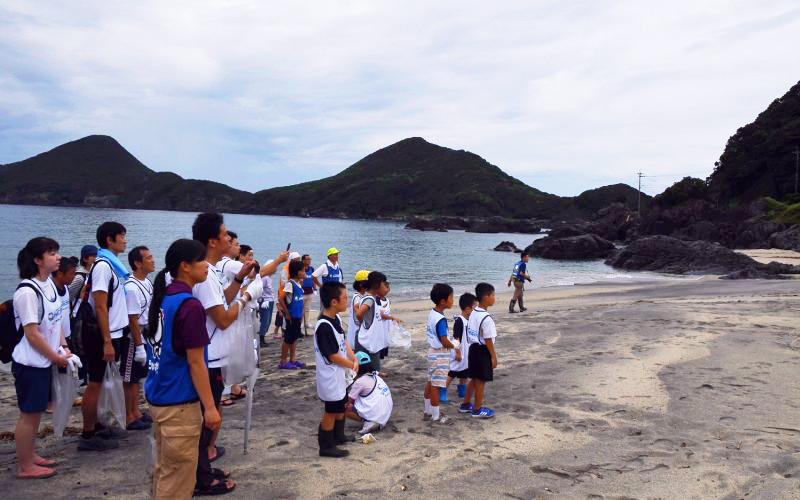 ウミガメの足跡と産卵場所を観察する参加者(写真)
