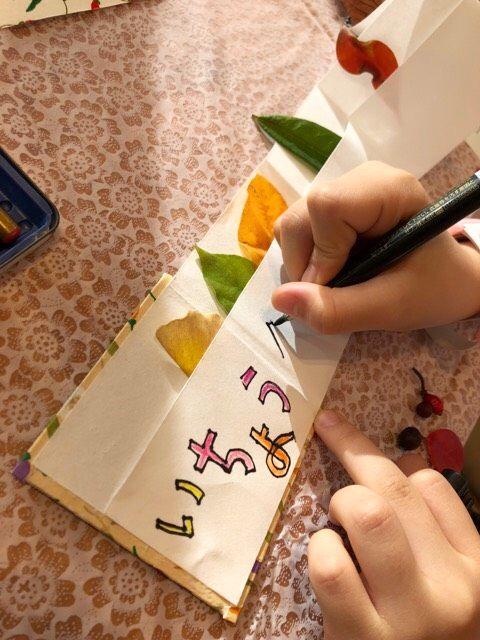 図鑑のポケットに葉っぱを入れタイトルを入れている写真
