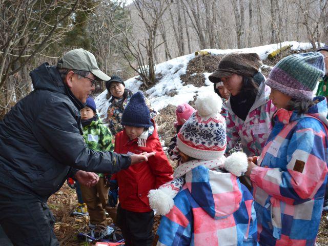 自然観察指導員の説明を聞く子どもの写真