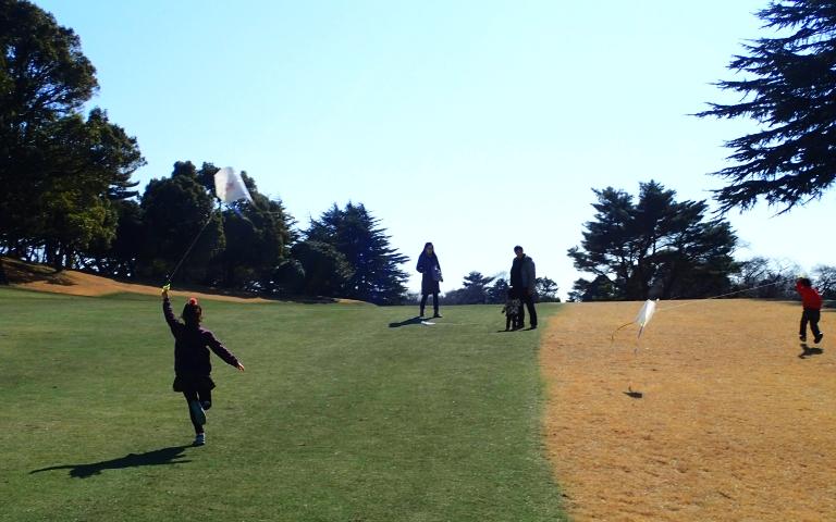 凧を揚げるためゴルフコース走る子供の写真