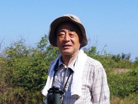 帽子を被り、双眼鏡を首からぶらさげている山﨑亨さん写真