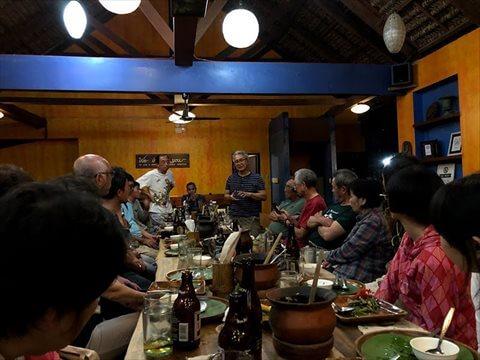 レストランでテーブルを囲む参加者と、テーブルの奥で自己紹介する人写真
