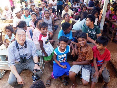 屋外の教室で大勢の子供たちと山﨑さん写真