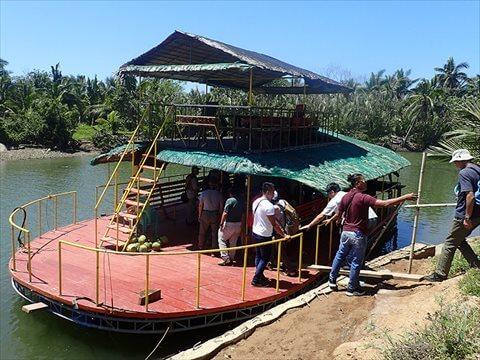 2階建てテント小屋が設えた観光船に乗り込む参加者写真