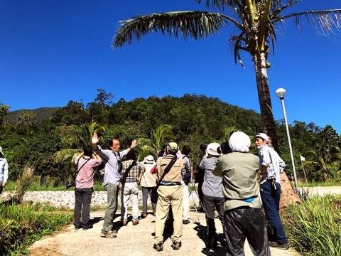 大きく手を広げて説明する山﨑さんと、青空に向かってカメラを向ける参加者の写真
