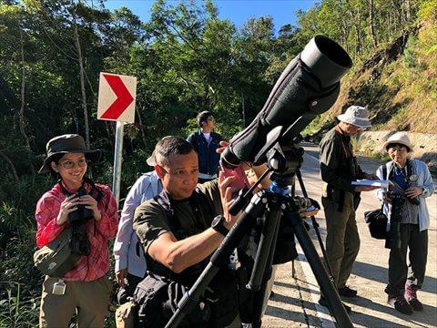 大きな望遠レンズのファインダー越しに、スマホで写真を撮るニッキさん写真