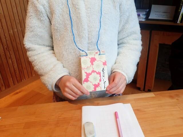 俳句ノートを首からぶらさげた写真