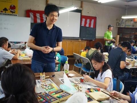 クラフト体験の講師と作業に熱中する参加者(写真)