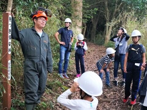 林業を営む佐藤太一さんとヘルメットを被った子どもたち(写真)
