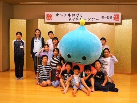 サニクリーングループの公式キャラクター「サニエル」と子どもたちで記念撮影