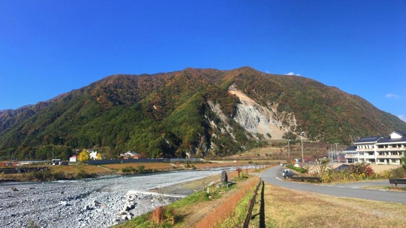 紅葉に色づいた山を正面に大鹿村の風景写真