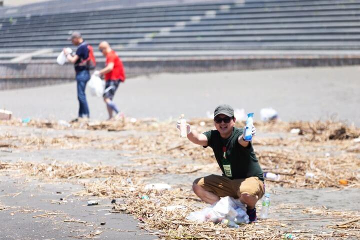 砂浜でゴミを両手に掲げる男性の写真
