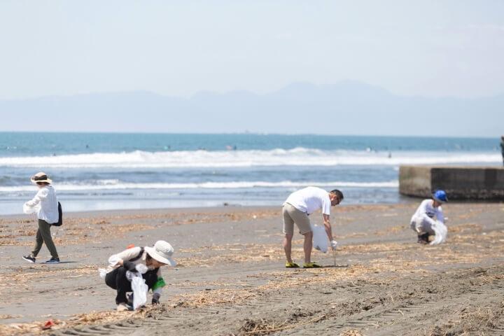 海岸で腰を屈めてゴミを拾っている参加者の写真