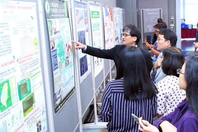 展示したポスターの内容を興味深く見る参加者と道家の写真