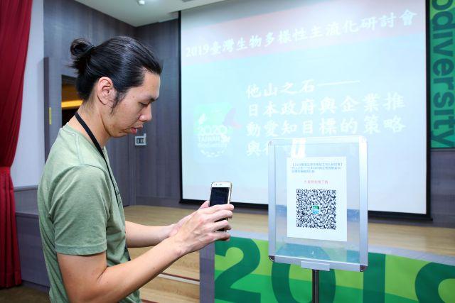 会場に設置されたQRコードにスマートフォンをかざす男性の写真