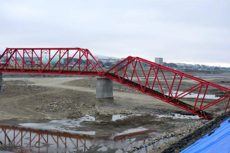 崩落した赤い鉄道橋の写真