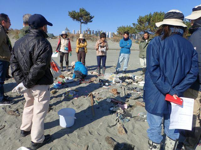拾ったゴミや貝殻を囲む参加者