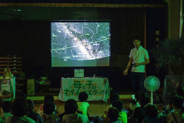 天体をスライドで解説する講師の写真