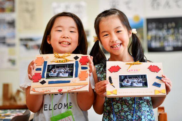 フォトフレームを掲げ津子供たちの写真