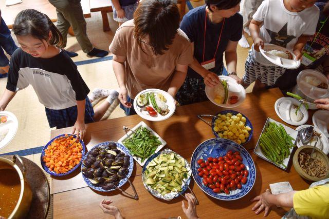 お皿にトッピングの野菜を盛る参加者の写真