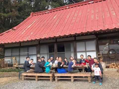赤い屋根の民家の庭先で食事する参加者の写真
