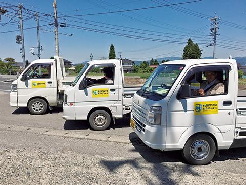 黄色いステッカーを貼った軽トラック3台の写真