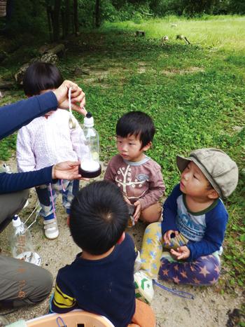 昆虫観察ボトルの中を覗く子供の写真
