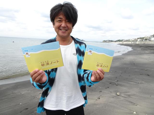 砂浜ノートを持つ鍵井靖章さんの写真