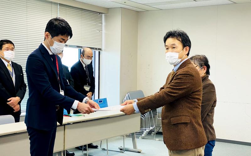 大野が熊本県の職員に要望書を手渡している写真
